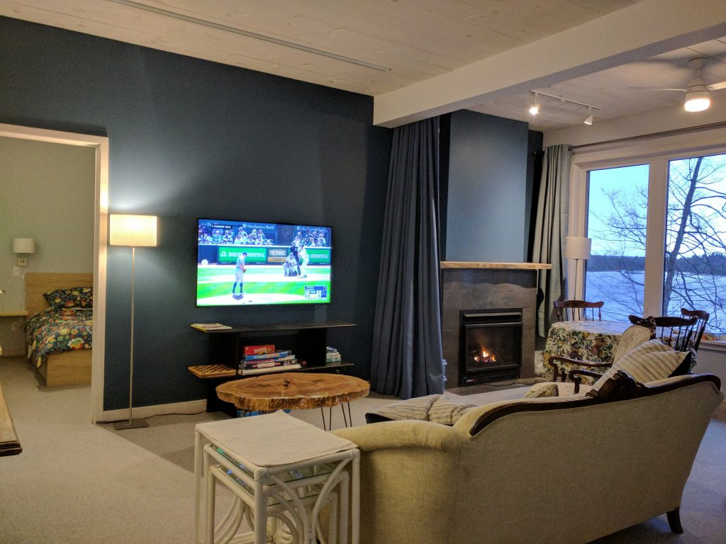Family room with fireplace, TV, games table, and king bed pulllout